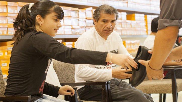 Una adolescente junto a su padre, en el momento de probarse los zapatos.