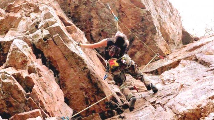 La joven salteña, escalando la empinada pared de una montaña.