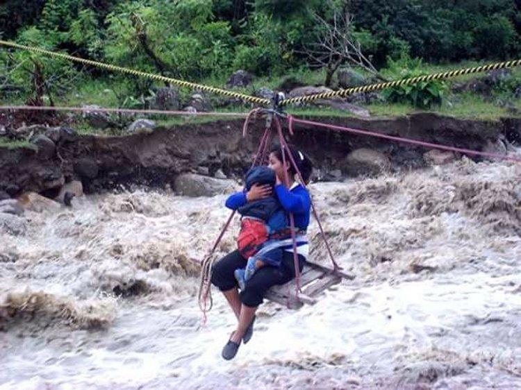Una mujer y su criatura cruzan el río en una roldana.