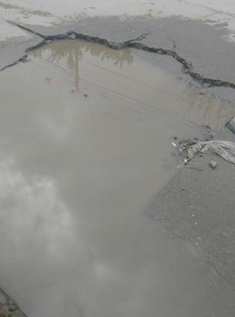 """De tanta agua que corre desde hace un año, el pavimento sufrió deterioro y los pozos son tan grades que podría """"comerse"""" un auto."""