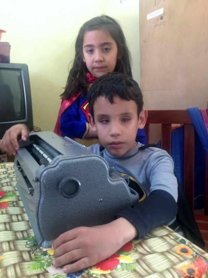 Bruno, abrazado a su máquina Braille, mientras su hermana vigila.