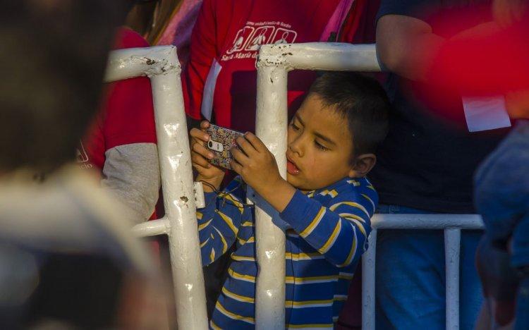 Un niño retrata todo a su paso, durante la procesión. Foto: Pablo Yapura