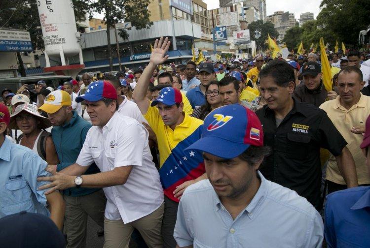 El opositor Henrique Capriles levanta su mano durante la marcha en Caracas. Foto: AP