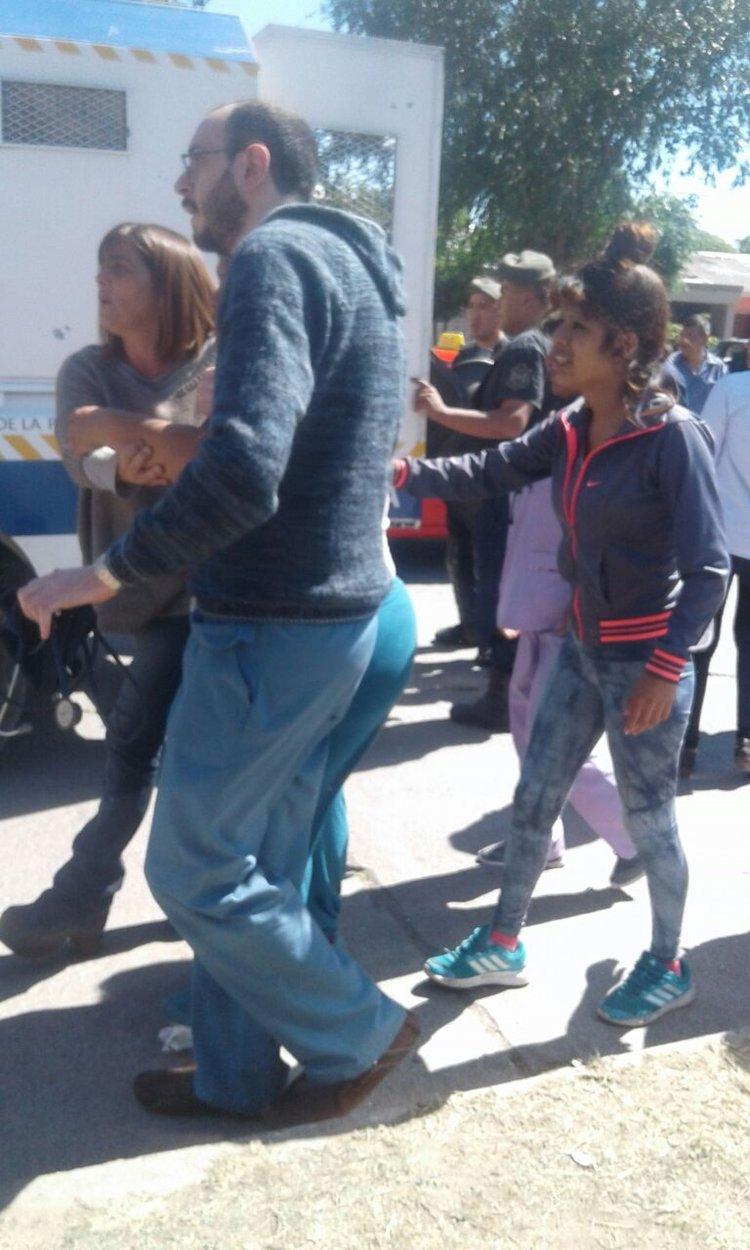 Dos personas que se encontraban en el lugar sujetan a la madre del nene atropellado.