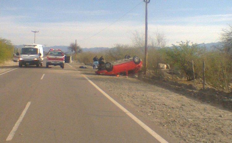 Los médicos, detrás del auto volcado, atienden a uno de los heridos del accidente vial ocurrido esta mañana.