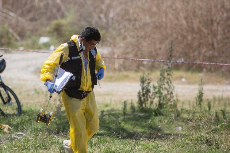 Uno de los peritos del CIF observando el lugar donde fue encontrado el cadáver de un joven.