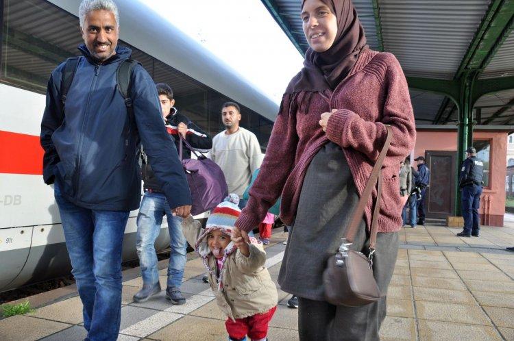 Una familia de inmigrantes camina por una plataforma de trenes en Eisenhüttenstadt, Alemania. Foto: AP