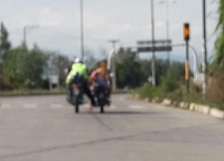 Otra infracción, el semáforo está en amarillo, y el policía de tránsito debió haber parado, siguió empujando la moto de las chicas y pasó en rojo.