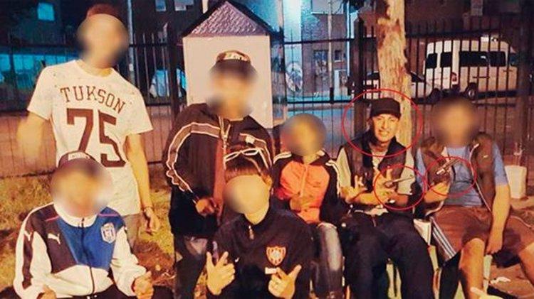 El hermano del sospechoso, en rojo, con una pistola en la mano.